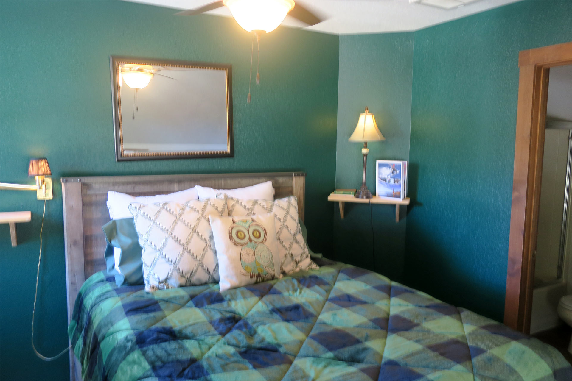 Queen-sized bed with an owl pillow at the Carriage house