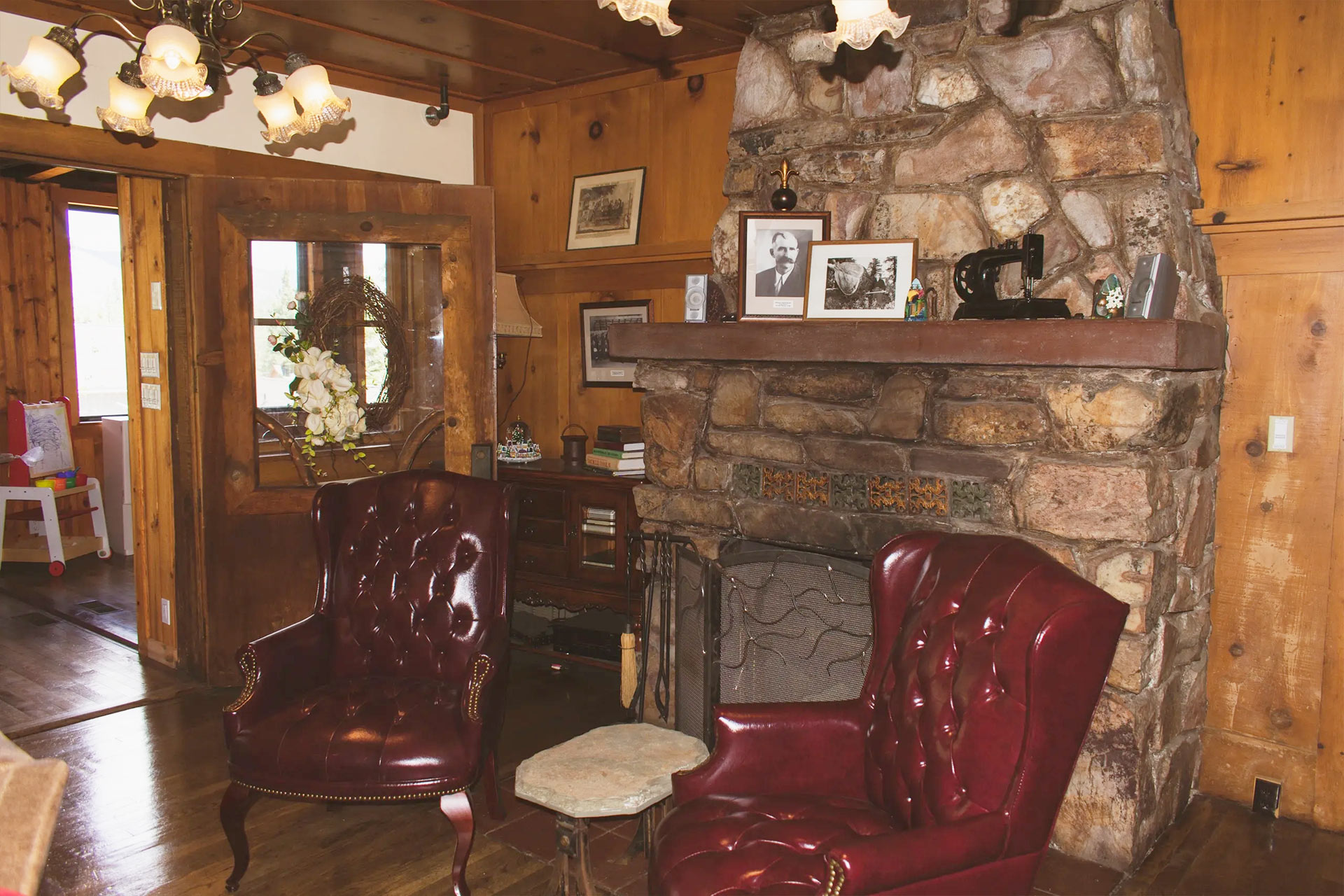 Stone fireplace with burgundy colored chairs in the Knickerbocker Mansion