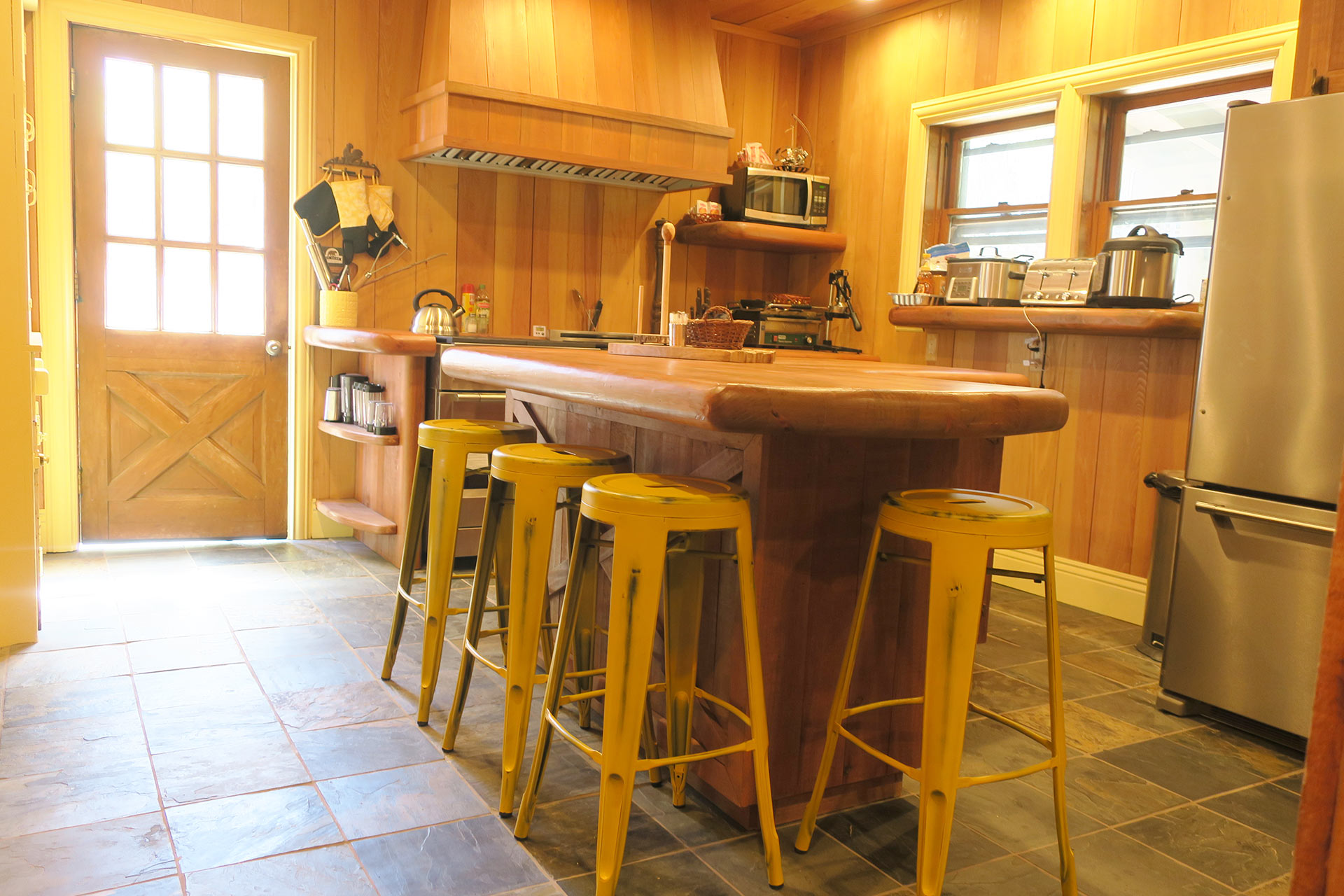 Knickerbocker mansion kitchen with yellow barstools for seating around the island