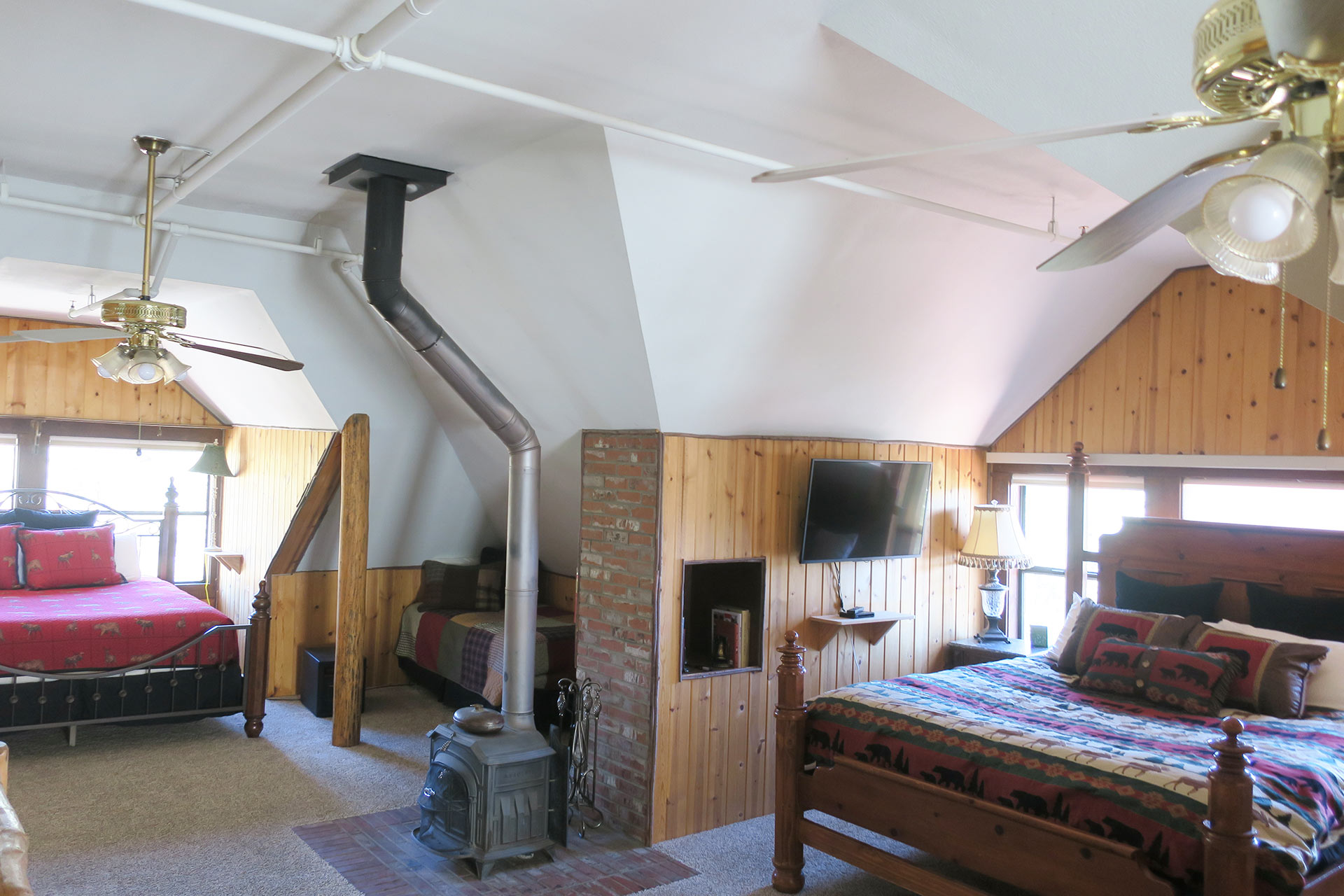knickerbocker mansion master suite with two beds and cast iron stove