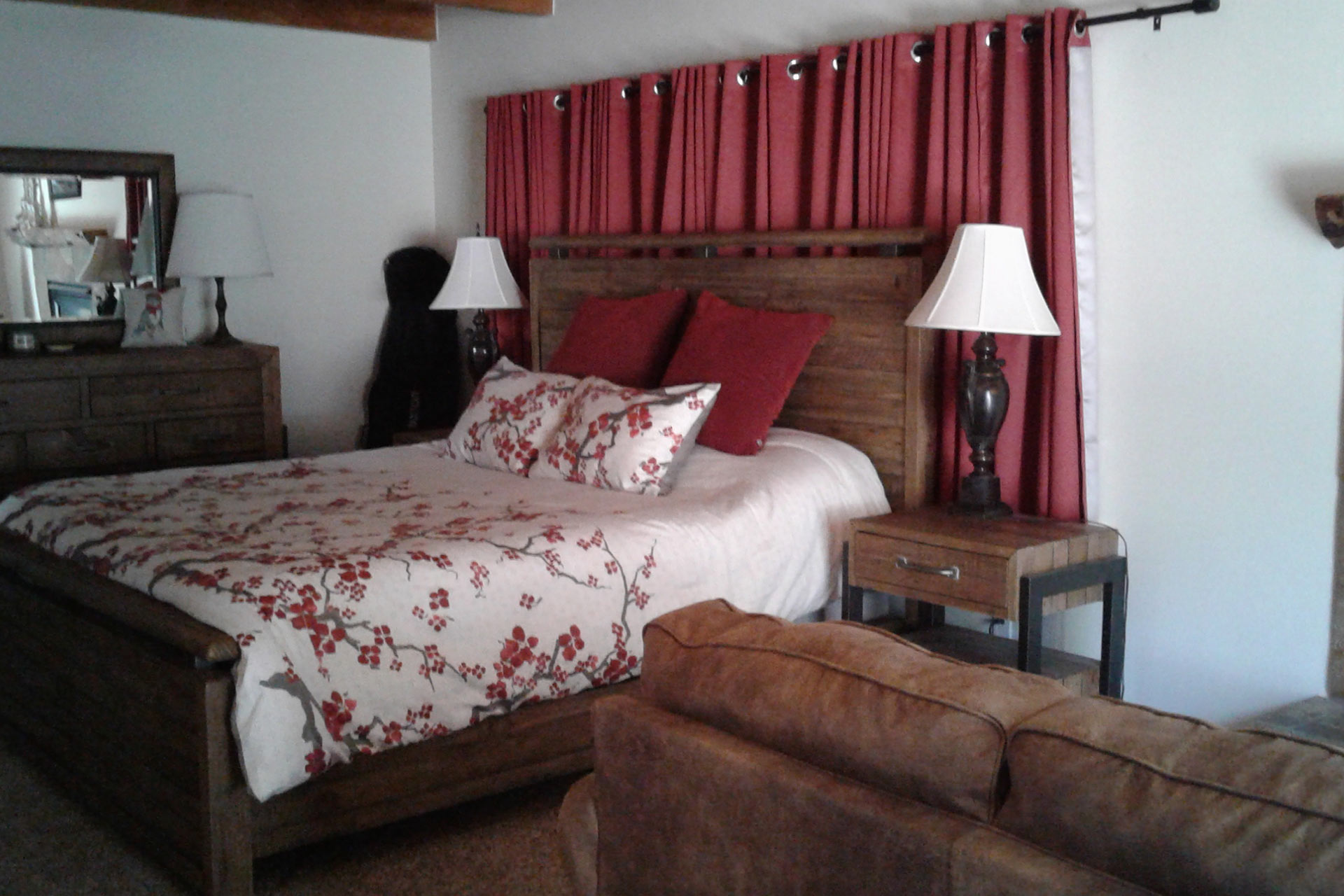 Master bedroom with red curtains at the residence